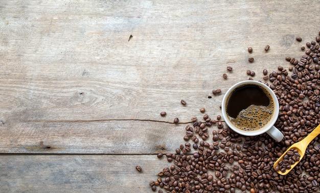 Filiżanka kawy i fasoli na drewnianej podłodze