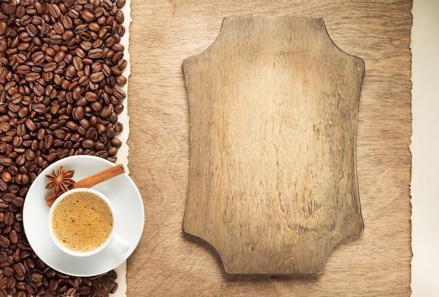 Filiżanka kawy i fasoli na drewnianym tle, widok z góry