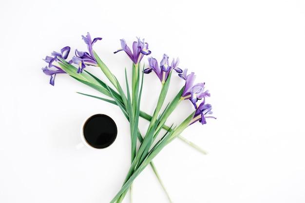 Filiżanka kawy i fioletowe kwiaty tęczówki na białym tle