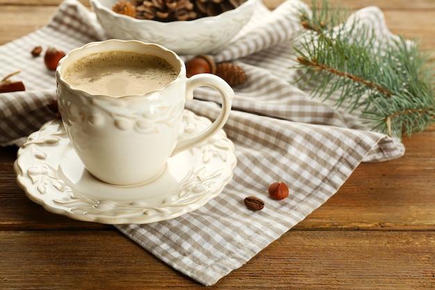 Filiżanka kawy i gałąź choinki na serwetce