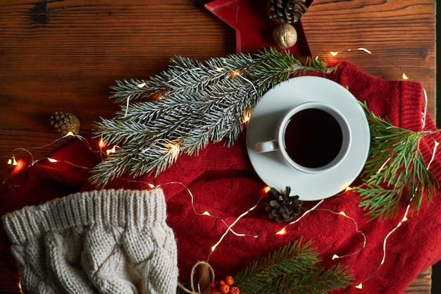 Filiżanka kawy i girlanda na drewnianej tacy z przytulnym czerwonym swetrem i ciepłą czapką. noworoczna martwa natura z gałązką jodły i jarzębiną