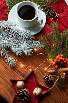 Filiżanka kawy i girlanda na drewnianej tacy z przytulnym czerwonym swetrem i ciepłą czapką. noworoczna martwa natura z gałązką jodły