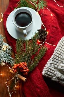 Filiżanka kawy i girlanda na drewnianej tacy z przytulnym czerwonym swetrem i ciepłą czapką.