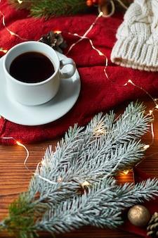 Filiżanka kawy i girlanda na drewnianej tacy z przytulnym czerwonym swetrem. noworoczna martwa natura z gałązką jodły i jarzębiną