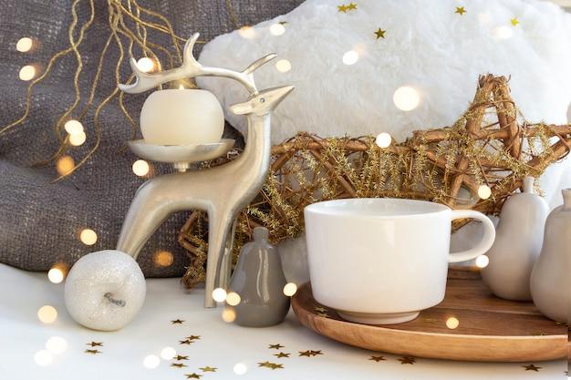 Filiżanka kawy i herbaty na świąteczny skład ze świecami, jeleniami i bombkami świątecznymi