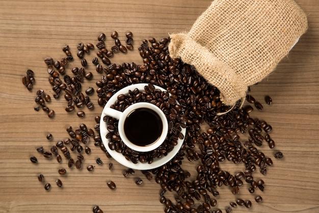 Filiżanka kawy i kawa na drewnianym stole. widok z góry.