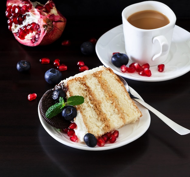 Filiżanka kawy i kawałek tortu ze świeżymi jagodami, twarożkiem i ciasteczkami czekoladowymi. ciemne tło drewniane. romantyczna koncepcja walentynki. skopiuj miejsce. poziomy baner