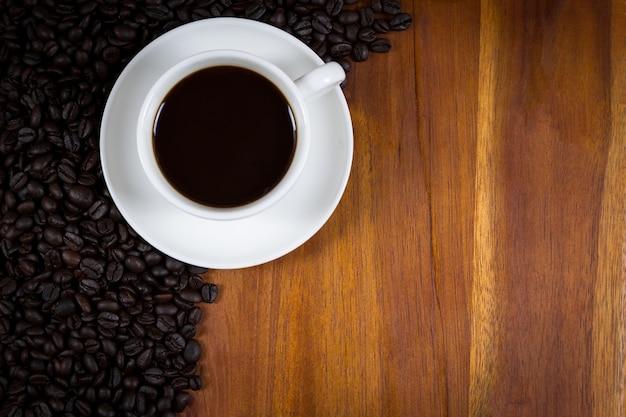 Filiżanka kawy i kawowe fasole na drewnianego tła odgórnym widoku.