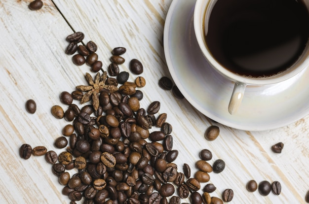 Filiżanka kawy i kawowe fasole na drewnianym