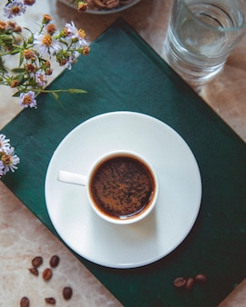 Filiżanka kawy i kawowe fasole na stole