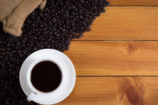 Filiżanka kawy i kawowe fasole w worku na drewnianym tle.