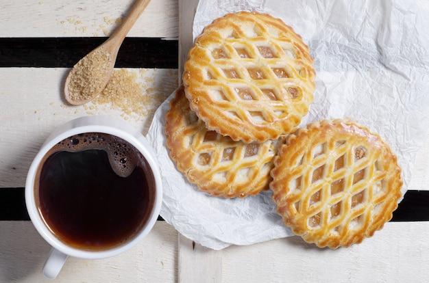 Filiżanka kawy i kratowe ciastka z nadzieniem jabłkowym