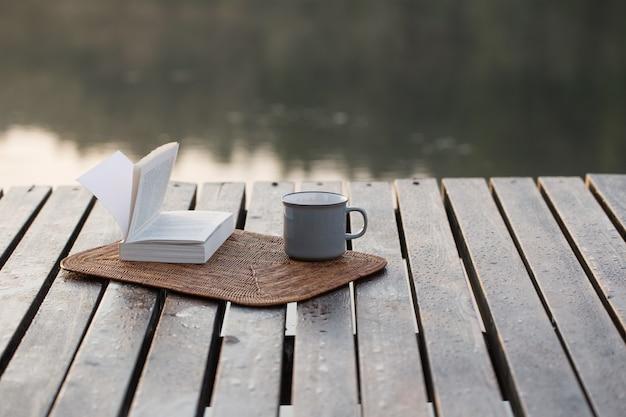 Filiżanka kawy i książka na drewnianym molo nad letnim jeziorem