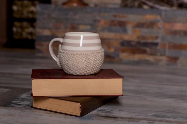 Filiżanka kawy i książka na drewnianym stole w natury tle