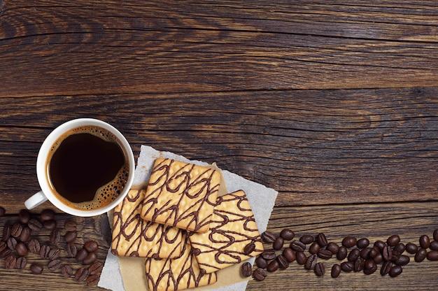 Filiżanka kawy i kwadratowe czekoladowe ciasteczka na starym drewnianym stole, widok z góry