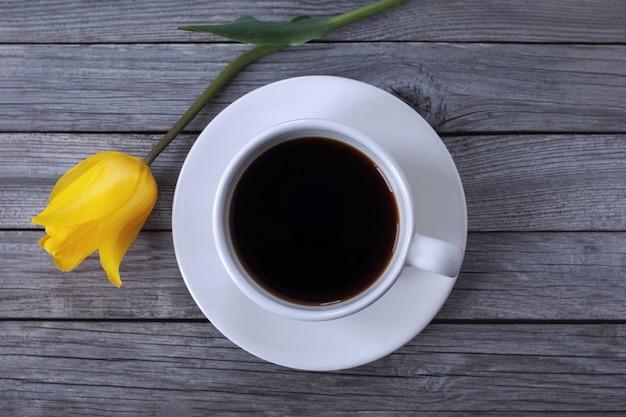 Filiżanka kawy i kwiat tulipana na drewnianym tle, wysoki kąt strzału