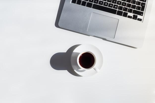 Filiżanka kawy i laptop na bielu stole