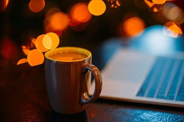 Filiżanka kawy i laptop na świątecznych dekoracji