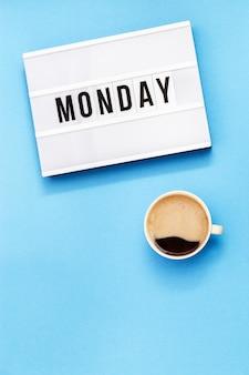 Filiżanka kawy i light box ze światowym poniedziałek