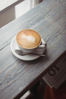 Filiżanka kawy i łyżka na drewnianym stole