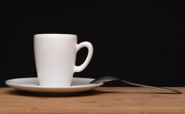 Filiżanka kawy i łyżka pod drewnianym stołem