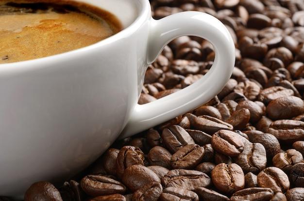 Filiżanka kawy i makro w tle ziaren kawy