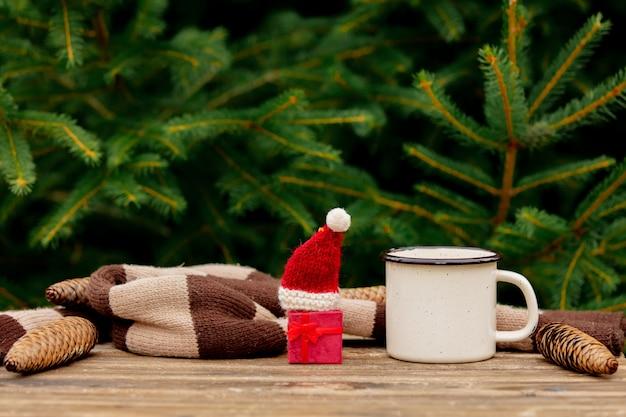 Filiżanka kawy i mały prezent na boże narodzenie w kapeluszu na drewnianym stole z gałęzi świerkowych na tle