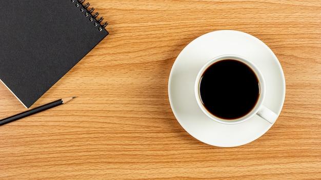Filiżanka kawy i notatnik na drewnianym biurowym biurku. - puste miejsce na tekst reklamowy.