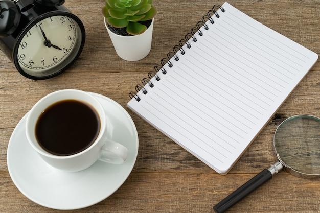 Filiżanka kawy i notatnik z miejscem na kopię na drewnianym tle
