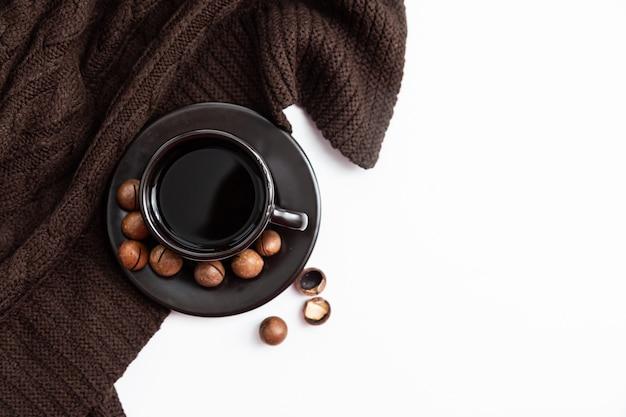 Filiżanka kawy i orzechów na tle z dzianiny koc brązowy