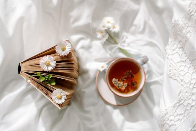 Filiżanka kawy i otwarta książka na białym otwartym łóżku. widok z góry poranne śniadanie. jasny, przytulny dzień