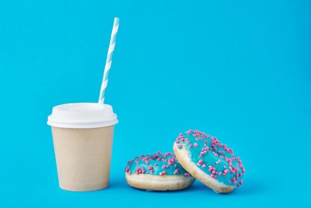 Filiżanka kawy i pączki na błękicie