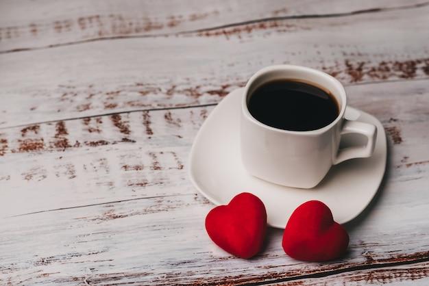 Filiżanka kawy i para czerwoni walentynka serca na białym drewnianym stole. pojęcie karty z pozdrowieniami