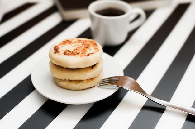 Filiżanka kawy i piekarnia na pasiastym czarny i biały tle.