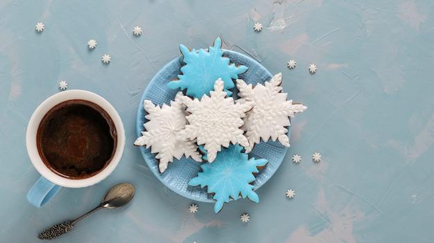 Filiżanka kawy i pierniki w kształcie płatków śniegu na jasnoniebieskim tle