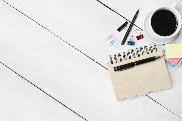 Filiżanka kawy i pióro, notatnik na biały drewniany biurko i miejsce na kopię.