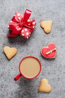 Filiżanka kawy i prezent, domowe ciasteczka serca z listem miłosnym na szarym stole. walentynki kartkę z życzeniami. widok z góry. format pionowy.