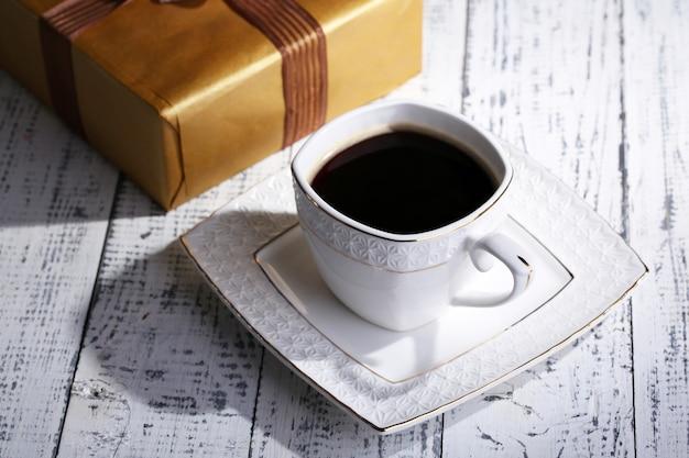 Filiżanka kawy i prezent na drewnianym stole z bliska