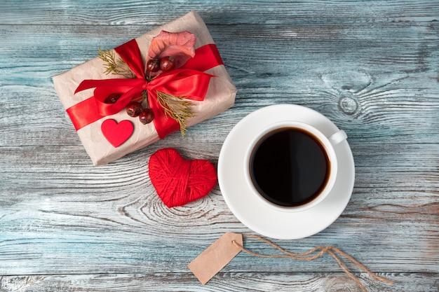 Filiżanka kawy i prezent z sercem 14 lutego. widok z góry z miejscem do skopiowania.