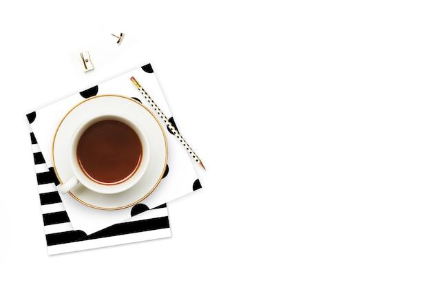 Filiżanka kawy i przedmioty na stole.