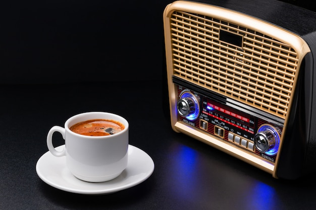 Filiżanka kawy i radiowy odbiorca na czarnym tle