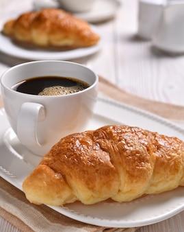 Filiżanka kawy i rogalik na drewnianym stole