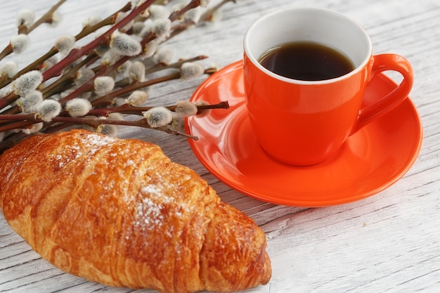 Filiżanka kawy i rogalika z wierzbą na białym drewnianym stole. romantyczna atmosfera