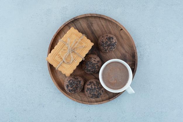 Filiżanka kawy i różne ciasteczka na drewnianym talerzu. zdjęcie wysokiej jakości