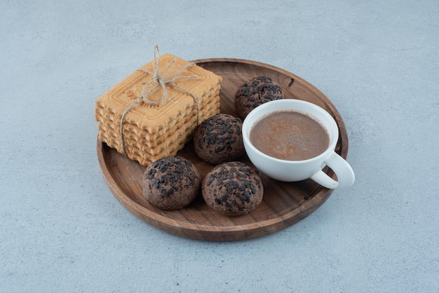 Filiżanka kawy i różne ciasteczka na drewnianym talerzu