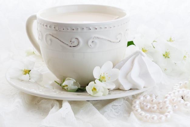 Filiżanka kawy i różowe kwiaty wiśni na białej ścianie
