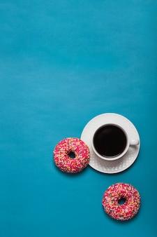 Filiżanka kawy i różowi pączki na błękitnym tle