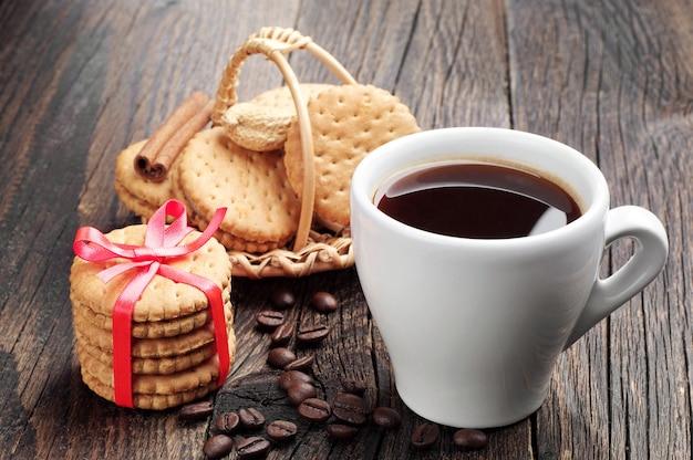 Filiżanka kawy i słodkie ciasteczka na drewnianym stole