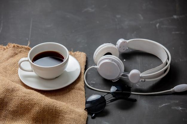 Filiżanka kawy i słuchawki z okularami przeciwsłonecznymi