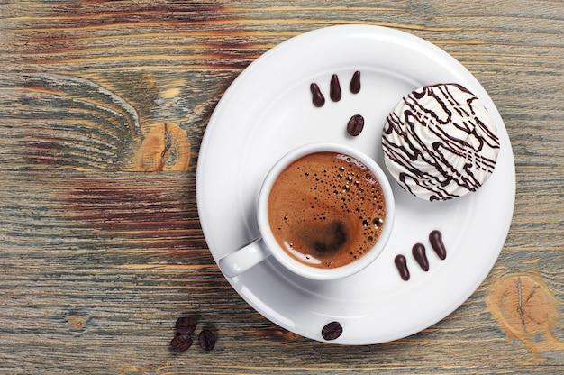Filiżanka kawy i smaczne ciasteczka na vintage drewnianym stole